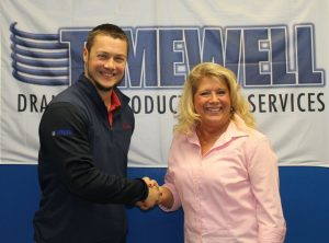 Darren Wagner (left) and Dawn Lucas (right) shake hands after announcing Timewell's purchase of Midwest Plastic Products.